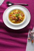 classic Icelandic Soup of shredded Lamb meat, vegetables and spices or kjotsupa served in soup bowl on table mat  with silver spoon on white wooden table, traditional recipe, vertical view from above
