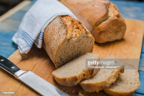 Sour dough bread on a chopping board with a knife (sliced)