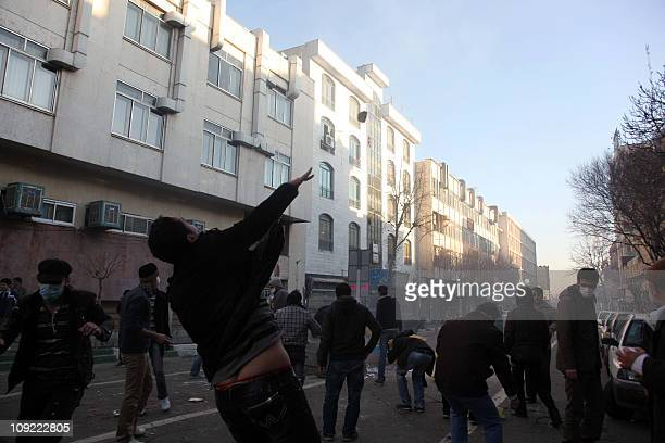 SOURCESAn Iranian ptotester throws a stone at riot police during an antigovernment demonstration under the pretext of rallies supporting Arab...