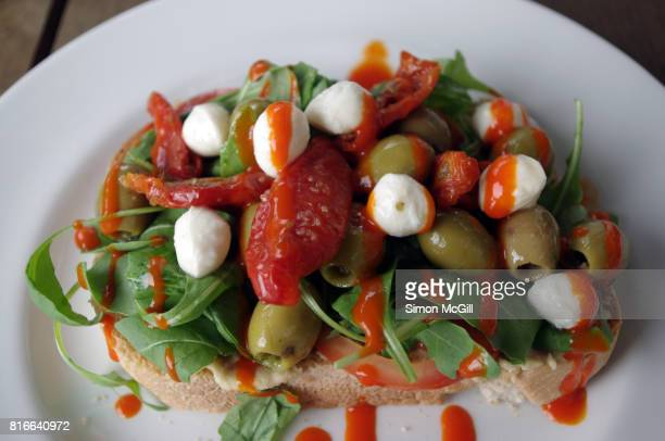 Sourdough bread topped with arugula leaves, green olives, sun-dried tomatoes and mini bocconcini cheese balls and a red pepper sauce on a round white plate