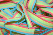 Sour flavored Rainbow strips covered in sugar randomly heaped.
