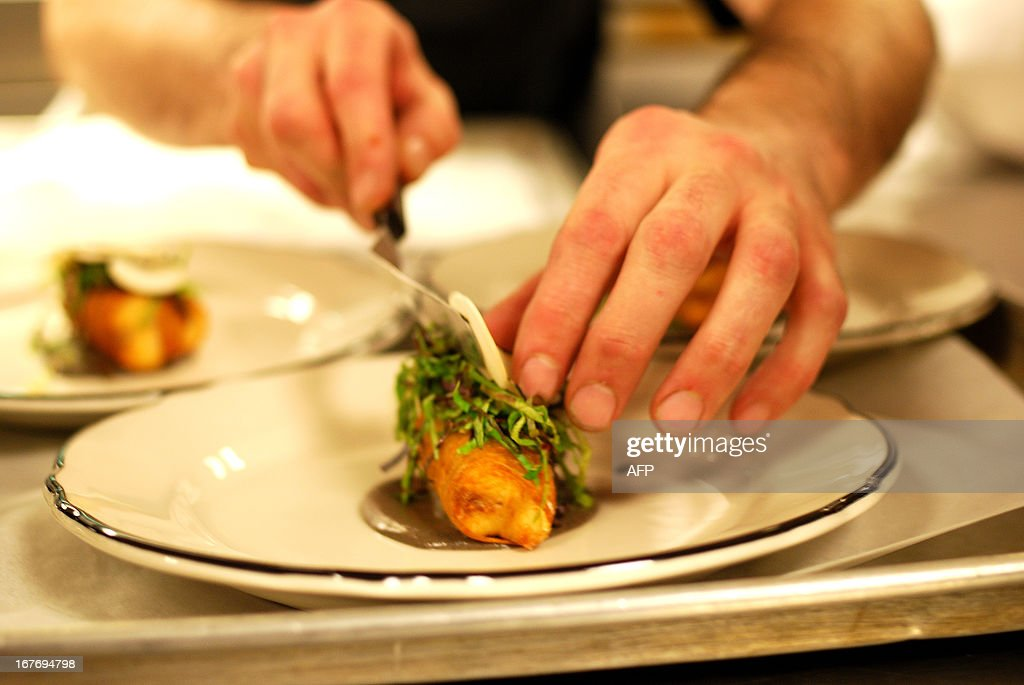 A sous chef places slivers of truffles and parmasean on a sea bass which has been wrapped in strands of potato and deep friend at a special event featuring chef Keisuke Matsushima of Nice at Chicago's Paris Club on April 25, 2013. Reproducing French cusine with American ingredients can be challenging, and even dedicated foodies aren't always willing to try French classics like frog's legs and escargots. AFP PHOTO / Mira OBERMAN