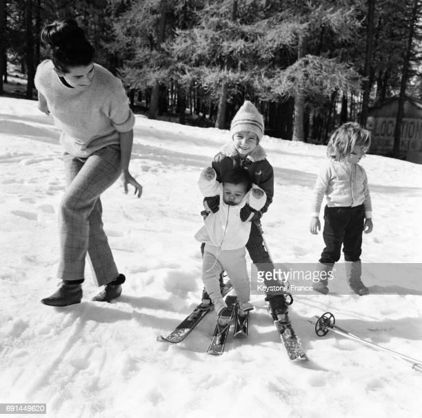 Soutenue par sa grande soeur la petite fille fait ses premiers pas à skis sous la surveillance de sa maman à Valberg France le 15 novembre 1966