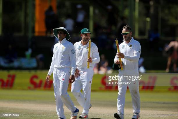South Africa batsman Dean Elgar Captain Faf du Plessis and bowler Keshav Maharaj hold one of the stumps after South Africa won on the third day of...