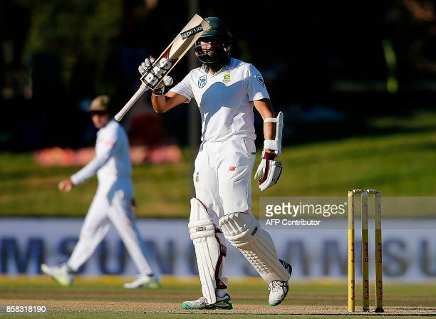South Africa batsman Hashim Amla raises his bat as he celebrates after scoring a halfcentury during the first day of the second Test cricket match...