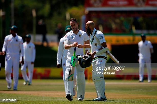 South Africa batsmen Faf du Plessis and Hashim Amla bump fists as the teams break for lunch during the second day of the second Test Match between...