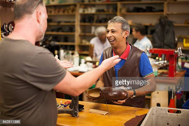 South Africa, Cape Town, cobbler and customer having fun