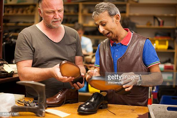 South Africa, Cape Town, cobbler explaning customer quality of his work