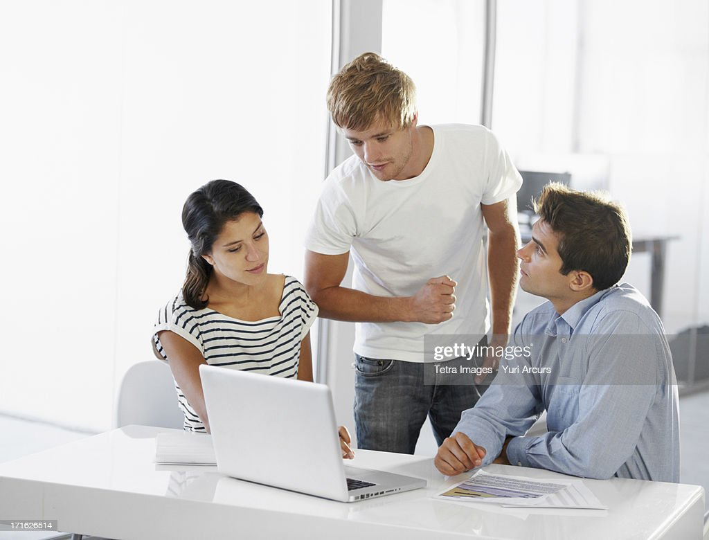 South Africa, Cape Town, Coworkers talking at table, using laptop : Stock Photo