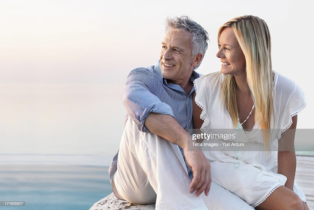 South Africa, Cape Town, Mature couple sitting by seashore
