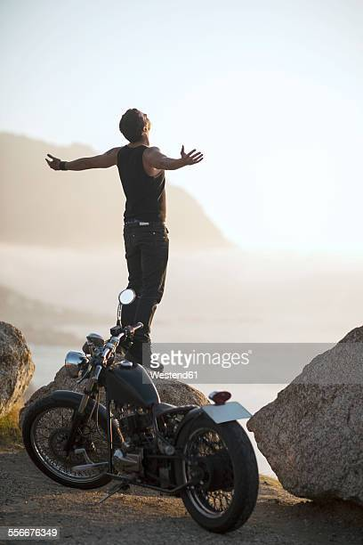 South Africa, Cape Town, motorcyclist standing on rock at the coast feeling free
