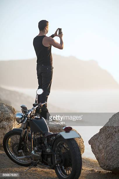 South Africa, Cape Town, motorcyclist standing on rock at the coast taking pictures