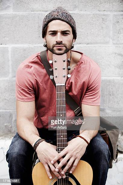 South Africa, Cape Town, Portrait of musician against brick wall