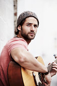 South Africa, Cape Town, Portrait of musician playing guitar outdoors