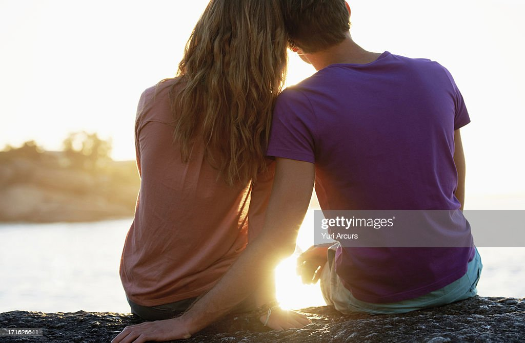 South Africa, Cape Town, Rear view of young couple sitting at beach : Stock Photo