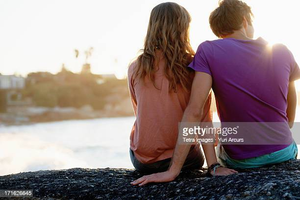 South Africa, Cape Town, Rear view of young couple sitting at beach