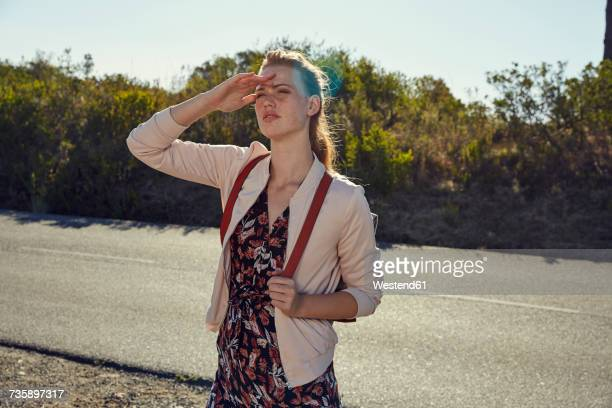 South Africa, Cape Town, Signal Hill, young woman on country road looking out