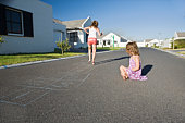 South Africa,  Cape Town,  two girls playing hopscotch on street