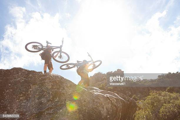 South Africa, Cape Town, young man and woman carrying mountain bikes on rocks