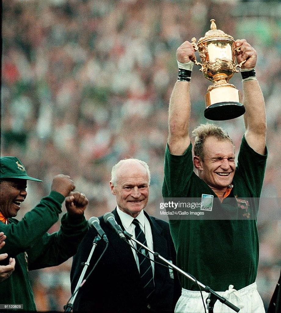South Africa. Captain of the Springbok team, Francois Pienaar holds the Web Ellis trophy up high after defeating the All Blacks at the World Cup. President Nelson Mandela dances in joy.