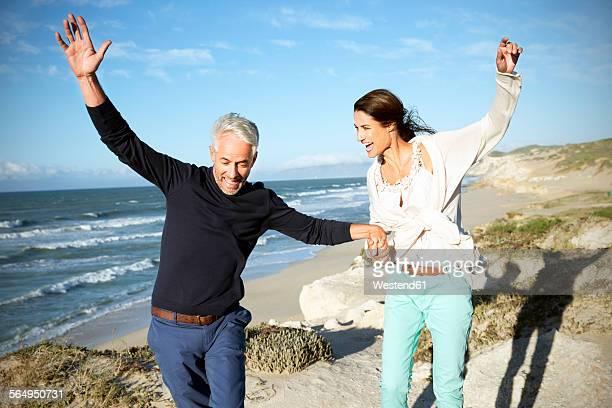 South Africa, couple balancing on walk along the coast