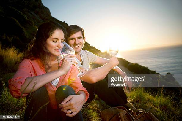South Africa, couple drinking white wine at the coast at sunset