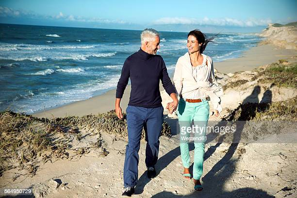 South Africa, couple walking along the coast hand in hand