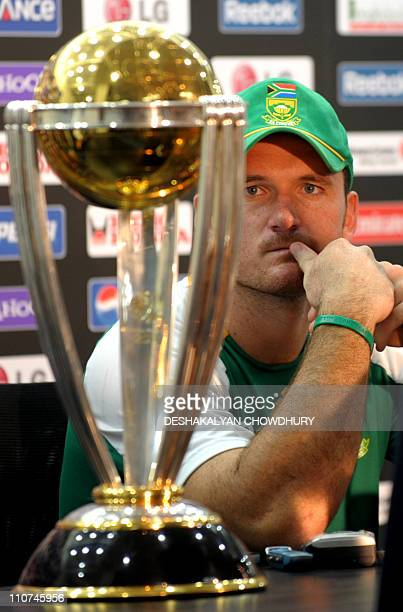 South Africa cricket team captain Graeme Smith sits near the Cricket World Cup 2011 trophy as he address a press conference after a team training...