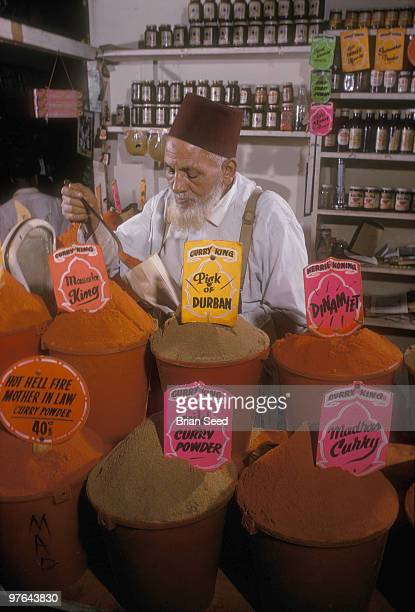 South Africa Durban Indian store with display of curry powders and owner filling a bag with curry powderCurry displayed MasalaMadras and Hot Hell...
