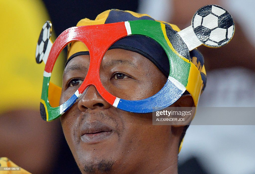 A South Africa fan cheers after South Africa beat Spain in a friendly football match at the Soccer City Stadium in Soweto on November 19, 2013. AFP PHOTO / ALEXANDER JOE