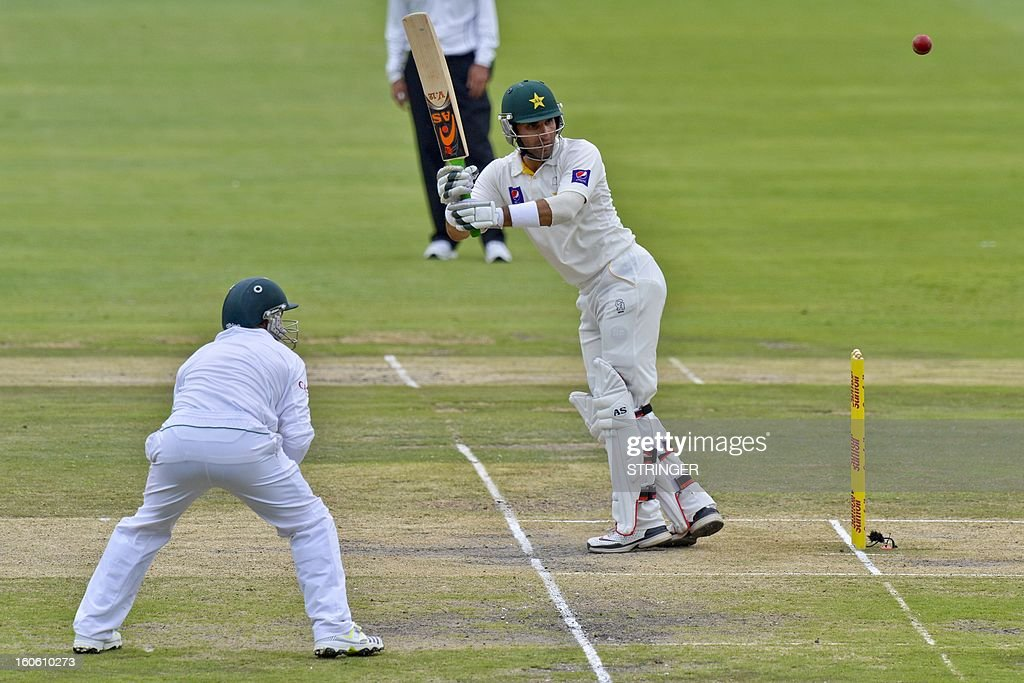 South Africa fielder, Dean Elgar (L) watches Pakistani batsman Misbah-ul-Haq hit the ball on day three of the first test match between South Africa and Pakistan in Johannesburg at Wanderers Stadium on February 3, 2013. AFP PHOTO / Stringer