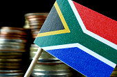 South Africa flag waving with stack of money coins macro