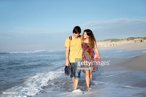 South Africa, happy couple wading in the ocean
