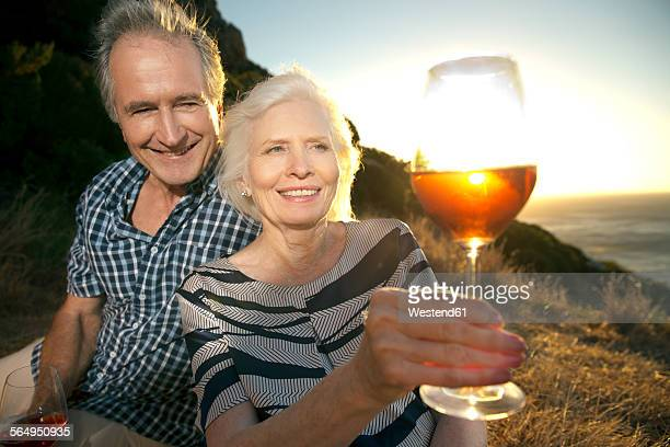 South Africa, happy senior couple with glasses of red wine by sunset