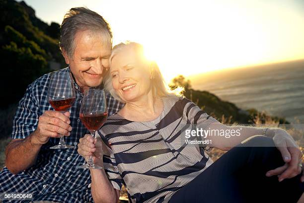 South Africa, happy senior couple with glasses of red wine