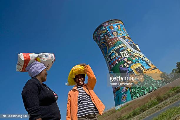 South Africa, Johannesburg, Soweto Two women chatting in front of Orlando Power Station tower