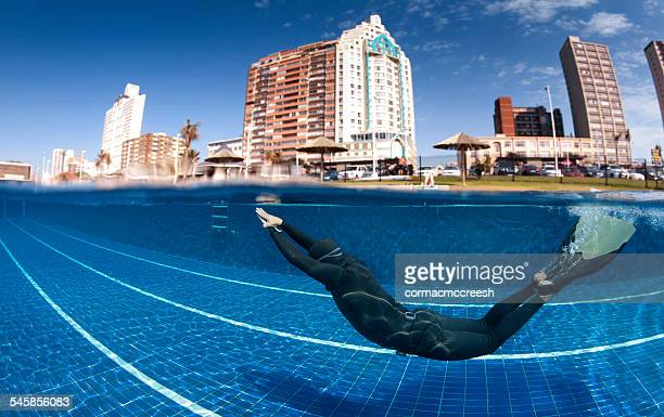 South Africa, KwaZulu Natal, Durban, Man wearing monofin diving in swimming pool with beachfront hotels in background