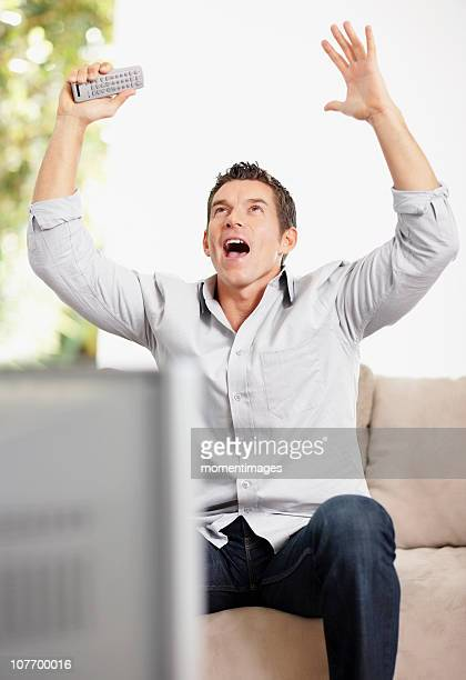 South Africa, Man cheering in front of television