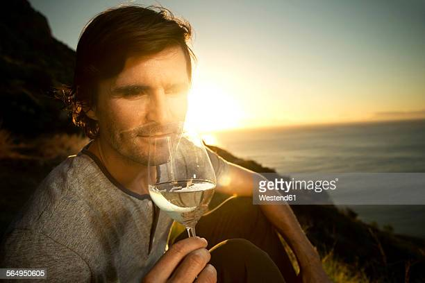 South Africa, man white wine at the coast at sunset