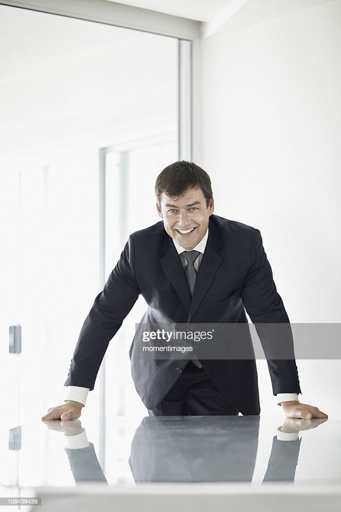 South Africa, Mid adult businessman in office smiling : Stock Photo