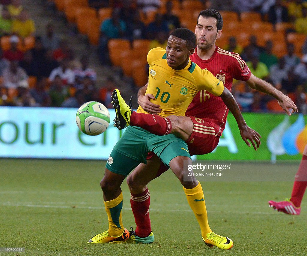 South Africa midfielder Lerato Chabangu (L) fights for the ball with Spain's midfielder Sergio Busquets during a friendly football match South Africa vs Spain at the Soccer City Stadium in Soweto on November 19, 2013. AFP PHOTO / ALEXANDER JOE