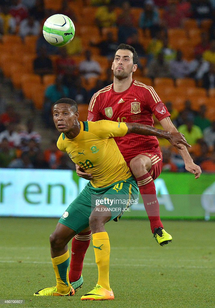 South Africa midfielder Lerato Chabangu (L) is challenged by Spain's midfielder Sergio Busquets during a friendly football match South Africa vs Spain at the Soccer City Stadium in Soweto on November 19, 2013. AFP PHOTO / ALEXANDER JOE