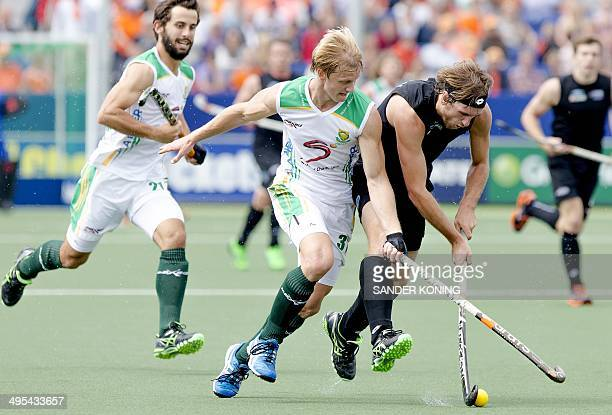 South Africa player Clinton Panther vies with New Zealand player Blair Hilton during a Field Hockey World Cup match in the Hague the Netherlands on...