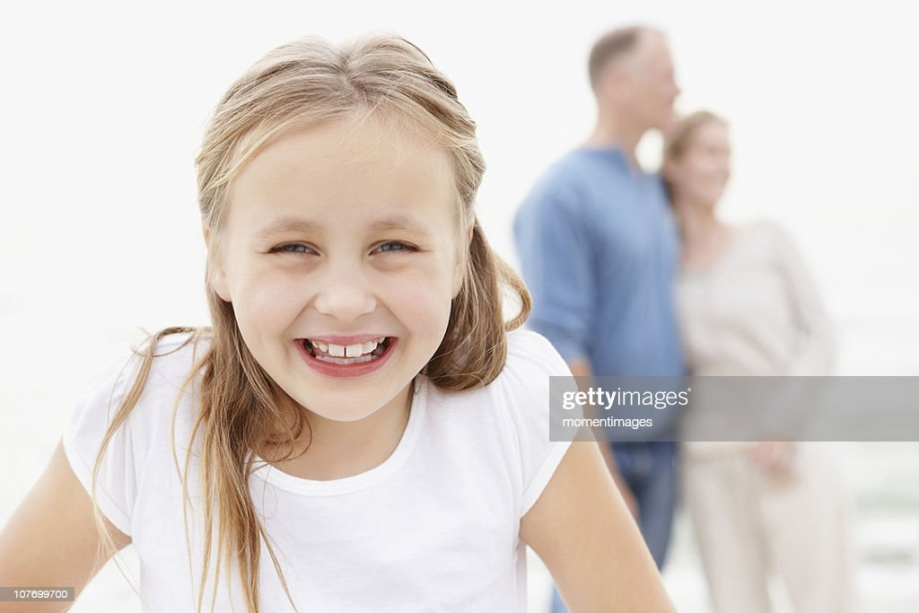 South Africa, Portrait of smiling girl (10-11), embracing couple in the background : Stock Photo