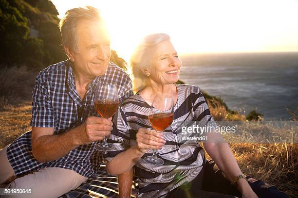 South Africa, senior couple with red wine glasses looking at view