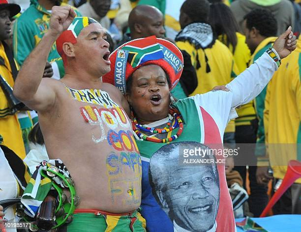 South Africa supporters celebrate after midfielder teammate Siphiwe Tshabalala scored the opening goal against Mexico during the Group A first round...