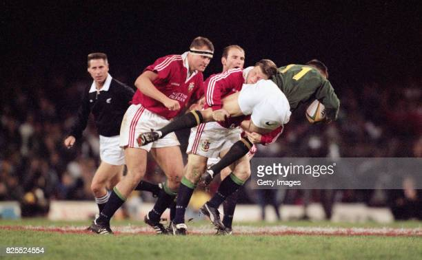 South Africa winger Andre Snyman is tackled by Scott Gibbs during the First Test Match between South Africa and British and Irish Lions at Newlands...