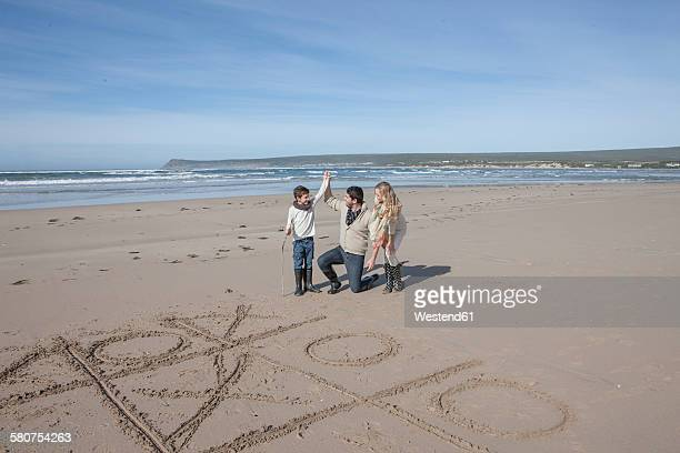 South Africa, Witsand, family playing tic tac toe on the beach