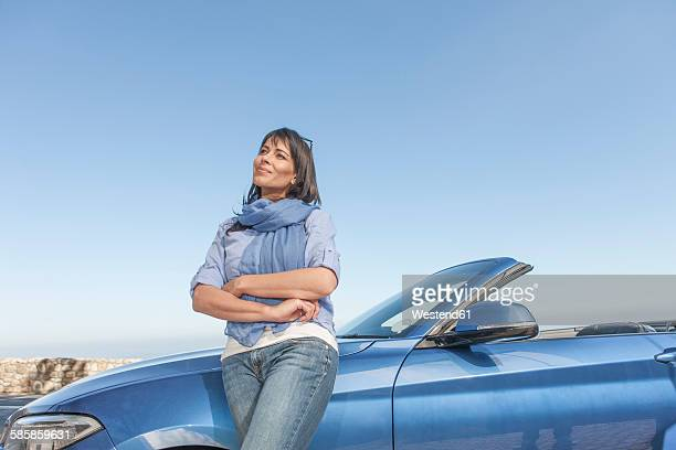 South Africa, woman standing next to a convertible