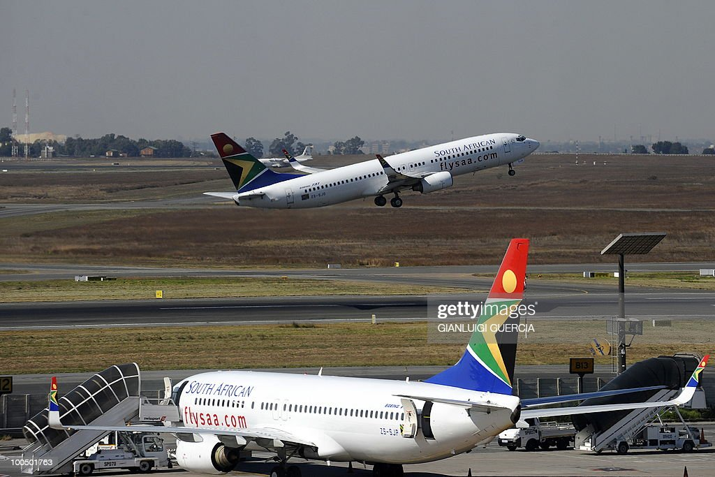 A South African airways flight takes off as another one is parked in a bay on the tarmac on May 25, 2010 at the Johannesburg O.R Tambo International airport in Johannesburg, South Africa. South Africa will host the FIFA World Cup 2010 from the 11th of June to the 11 of July.